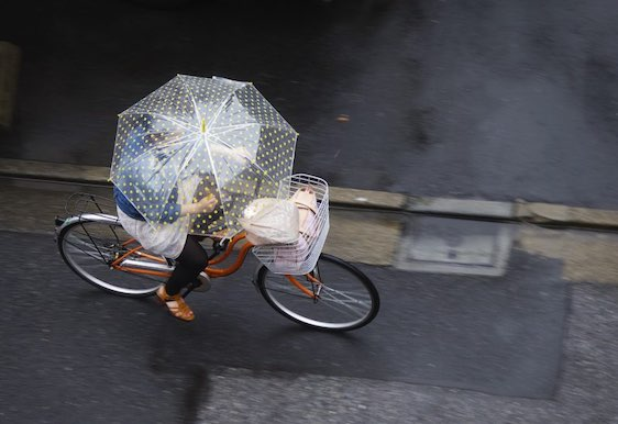 Tokyo, Japan - May 29, 2011: A Japanese woman rides her bicycle while holding an umbrella on a rainy Sunday in the Ojima area of Tokyo.
