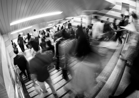 busy commuters running down the stairs of the station