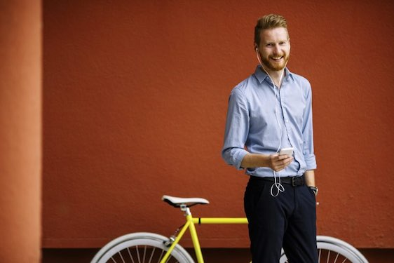 Handsome male listening music on cell phone. Bicycle on red wall