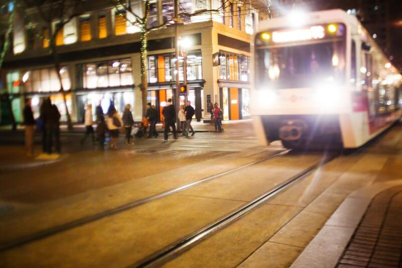 Portland, Oregon, USA - December 3, 2011: The Trimet MAX light rail runs through downtown Portland at night while pedestrians cross the street.