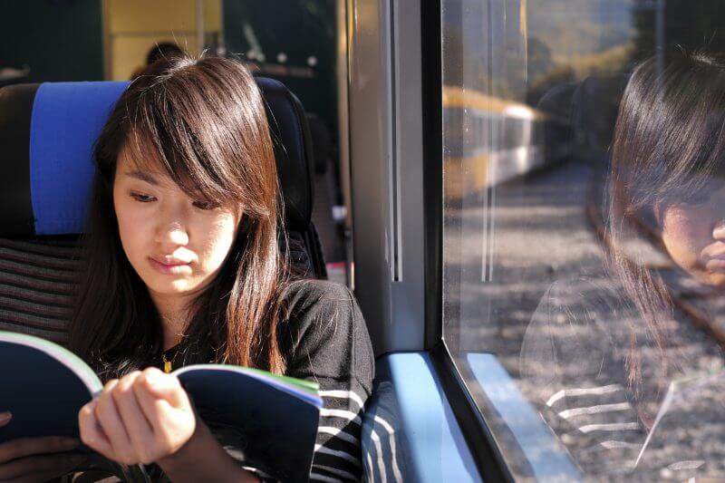 A female passenger is reading book on train