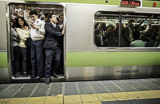 Tokyo, Japan - October 27, 2012: Passengers inside an overcrowded Yamanote Line train at rush hour in Tokyo Japan. Accounting the subway lines and all the other railways that operate in Tokyo 40 million people travel with this kind of transportation everyday in the city.