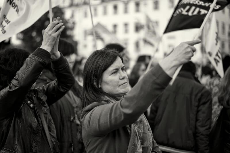 """Lisbon, Portugal - January 26, 2013: A woman waves a flag during a protest rally in Lisbon downtown, against the Education policy of the government."""