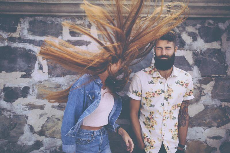 Retro style image hipster guy standing next to a hipster girl flinging her red hair wildly