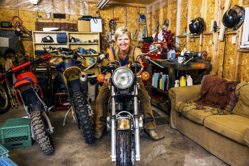 A pretty middle-aged woman in her garage full of motorcycles, dirt bikes and tools.  She is sitting astride a vintage motorcycle while smiling and looking at the camera and making eye contact. An authentic scene with a real person.