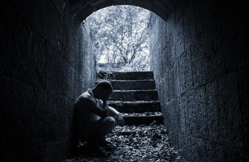 Young sad man sitting inside of dark stone tunnel, blue tonal correction photo filter effect