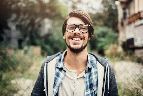 Outdoor portrait of a handsome young man with glasses.
