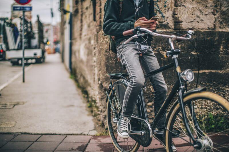 Young man enjoys bicycle ride in the city while using his mobile phone and surfing the net