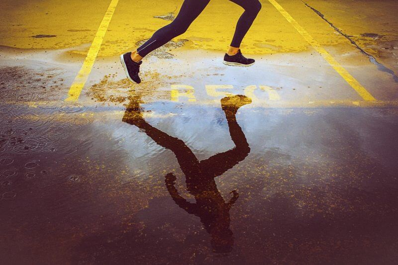 Young person running over the yellow parking lot. Black sport clothing - sport shoes, running tights, and a jacket. High angle view of a runner's legs and its reflection in the water.