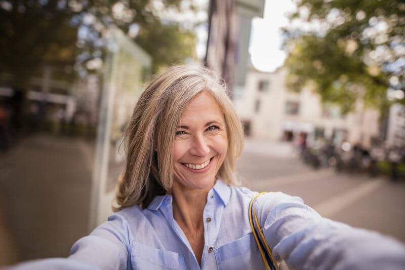 Beautiful smiling mature woman with grey hair taking a selfie while standing on a city street