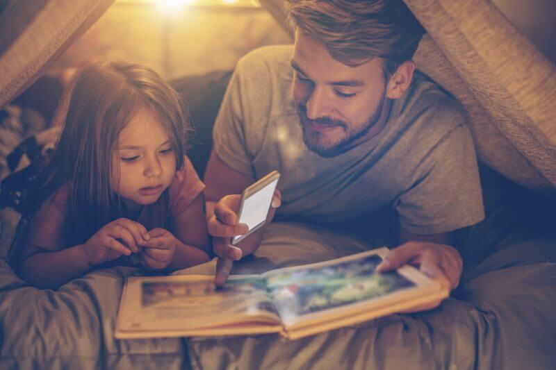 Father and daughter enjoying at home. Lying on bed at night in do it yourself tent and reading book together, using smart phone as light .