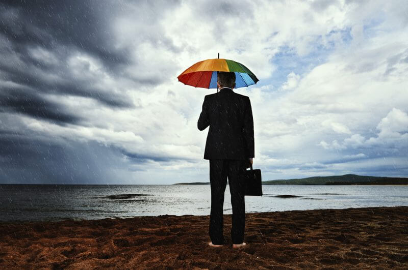 rear view of business man walking alone on the beach in stormy weather, holding briefcase and looking at the sea.