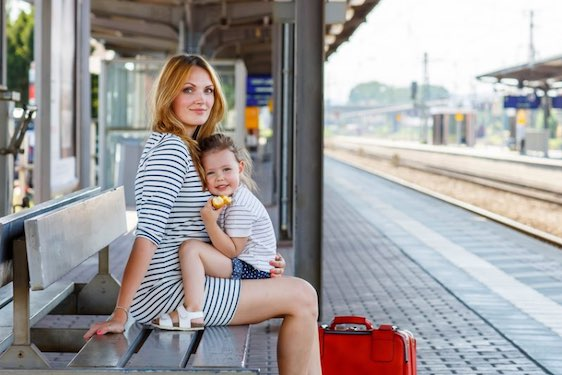 Cute little girl and her mother on a railway station. Kid and woman waiting for train and happy about a journey. People, travel, family, lifestyle concept