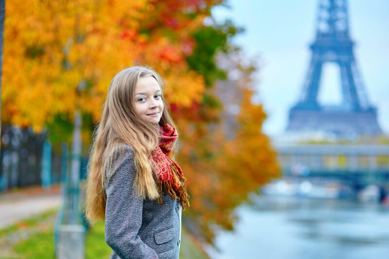 Beautiful young woman in Paris walking on the Isle of the Swans on a beautiful colorful autumn day, Eiffel tower in the background
