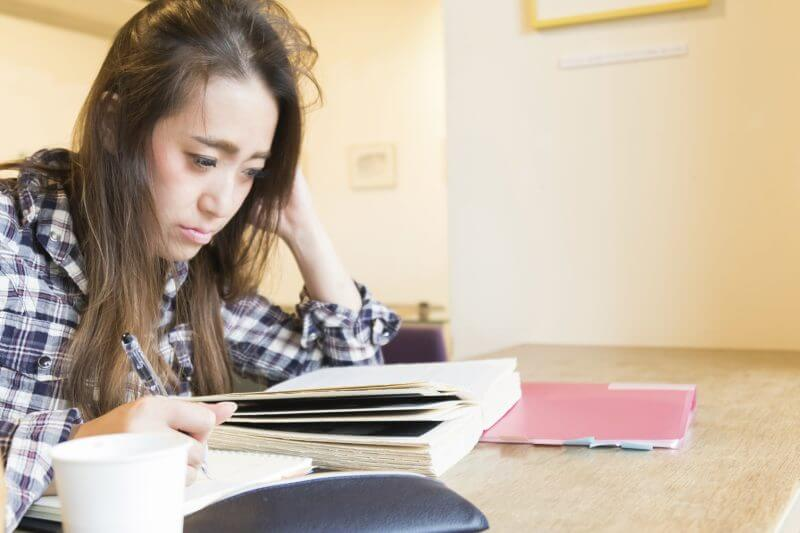 Japanese Student Studying at her college library before her examination.