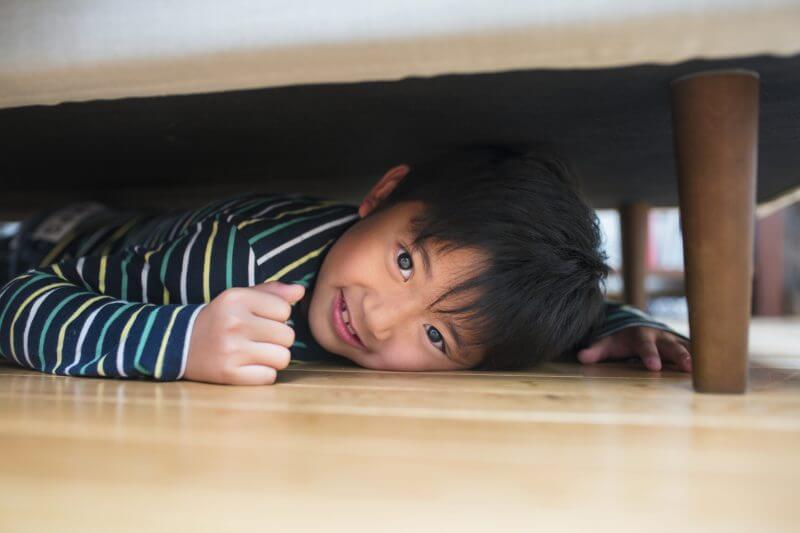 Young boy with a mischievous smile on his face hiding under the sofa. Kyoto, Japan. May 2016.